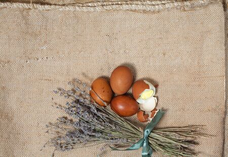 Easter eggs and a bouquet of lavender on a natural linen background
