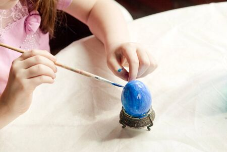 a 6 year old girl paints on an Easter egg