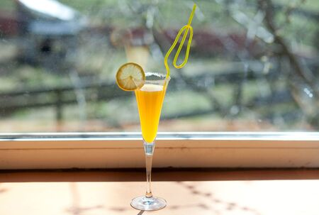 yellow cocktail with lemon in a glass