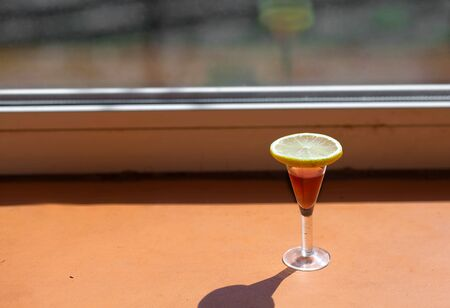 a glass of cognac with lemon in natural light from the window