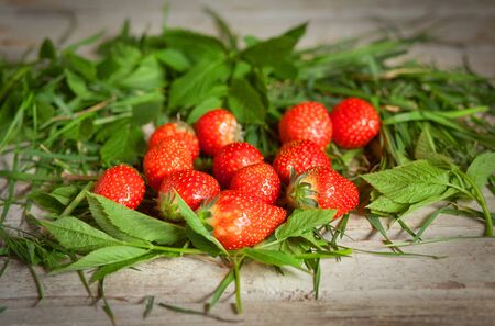 ripe strawberries in a handful on a wooden table Banque d'images