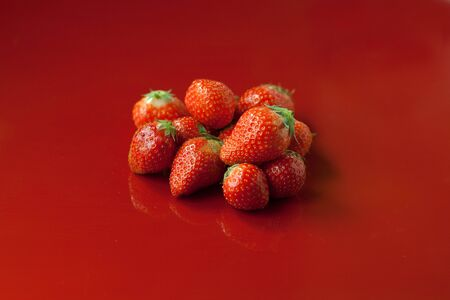 fresh ripe strawberries on a red background