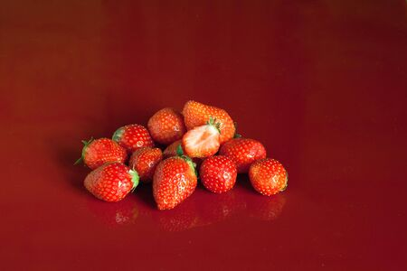 a handful of fresh strawberries on a red background