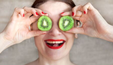 a girl with red lipstick eats a ripe kiwi and jokes with a fruit close up