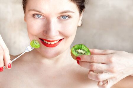 girl with red lipstick eats a ripe kiwi close up Banque d'images