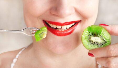 girl eats a ripe kiwi close up