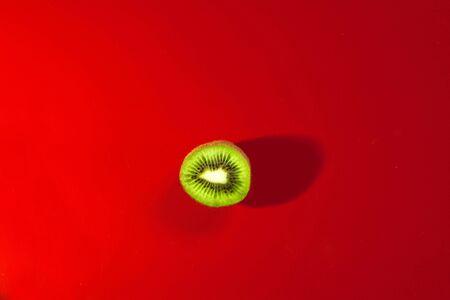 ripe juicy cut kiwi on a red background