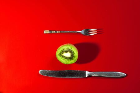 ripe kiwi and Cutlery on a red background