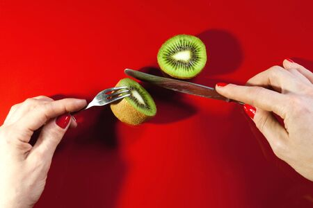 hands of a girl who eats a ripe juicy kiwi on a red background Banque d'images