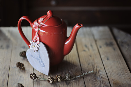 deer in heart: Red tea pot with wooden heart shaped decoration with deer