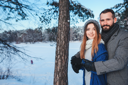 christmas spending: happy loving couple walking in snowy winter forest, spending christmas vacation together. Outdoor seasonal activities. Lifestyle capture. Stock Photo