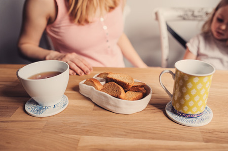 pyjama: pregnant mother and toddler daughter having breakfast at home, cozy lifestyle