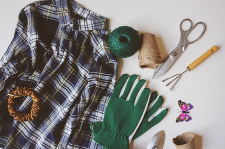 gardener still life composition with spring preparations for yard work and transplanting. Plaid shirt, gloves, tools, peat pots on white background. Top view, flat lay.