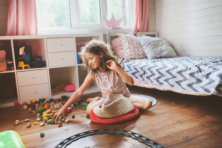 child girl cleaning her room and organize wooden toys into knitted storage bag. Housework and help concept Stockfoto - 96907051