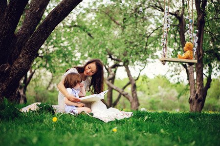 loving mother reading book to toddler son outdoor on picnic in spring or summer park. Happy family and mothers day concept