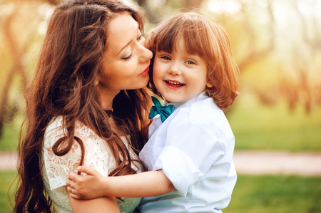 happy mom hugs and kiss toddler kid son outdoor in spring or summer. Loving family and mothers day concept.
