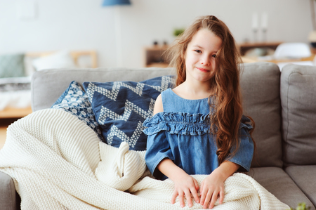 cute little child girl relaxing at home, sitting on couch, wrapped in cozy blanket. Kids health and seasonal flu healing concept Stock Photo