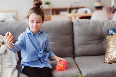 cute little child girl with mirror and cosmetic bag checking hairstyle at home. Pretend play and funny kids concept