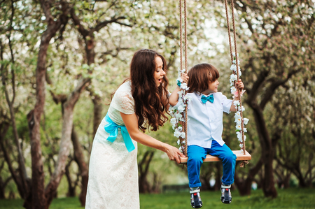 happy dressy mother and toddler child son having fun on swing in spring or summer park, wearing bow tie and long lacy dress for birthday or mothers day Stock Photo