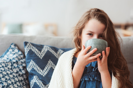 child girl drinking hot tea to recover from flu. Healing kids and protect immunity from seasonal virus, health concept