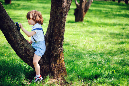 cute toddler child boy with long hair in stylish outfit playing with toy car on the walk in summer or sping garden, sitting on big tree Imagens