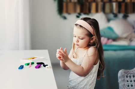 cute toddler girl playing with plasticine or play dough at home. Child learning to work with modelling clay Stock Photo