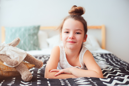 happy little child girl lying on her bed in the morning, waking up in comfortable room with modern bedlinen and pillows, cozy homely scene  Stock Photo
