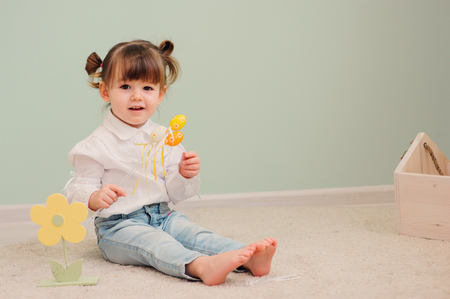 close up indoor portrait of cute happy baby girl playing with easter decorations Stock Photo
