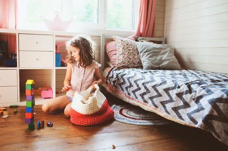 Niña limpiando su habitación y organizando juguetes de madera en una bolsa de almacenamiento tejida. Concepto de tareas domésticas y ayuda