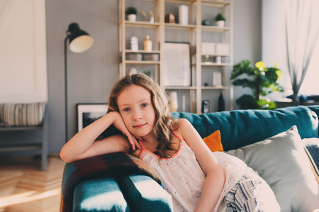 cute kid girl relaxing at home in cozy weekend morning in sunny living room with modern scandinavian interior