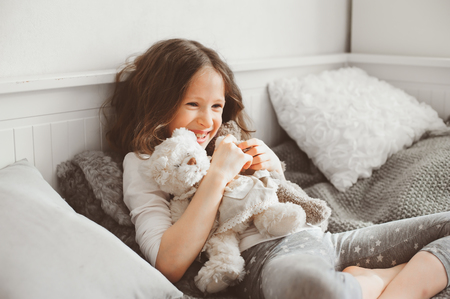 happy kid girl playing with teddy bears in her room, sitting on bed in pajama Stock Photo