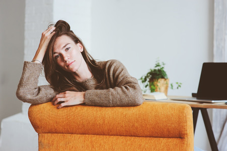 indoor portrait of beautiful feminine thoughtful young women alone in the room.  Stock Photo
