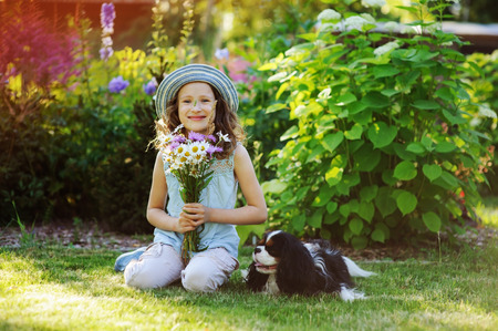 happy child girl relaxing in summer garden with her spaniel dog, wearing gardener hat and holding bouquet of flowers. Blooming perennials on background.