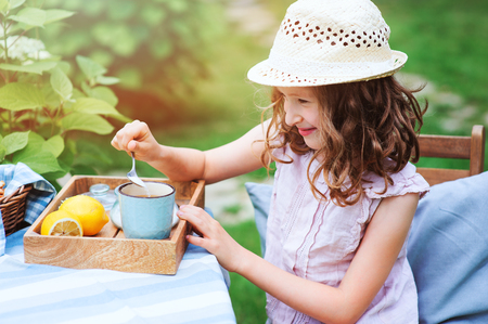 happy child girl drinking tea with lemons in summer garden in the morning.  Stock Photo