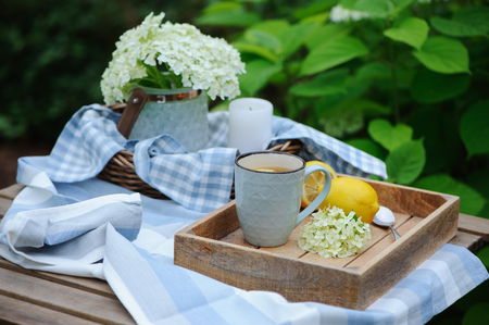 Summer breakfast in beautiful blooming garden. Tea with lemon, hydrangea flowers on wooden table with green background. Summertime and country slow living concept Stock Photo