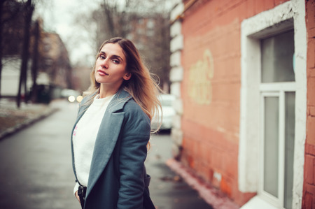 street style portrait of young woman walking in city in autumn or winter in warm coat Stock Photo