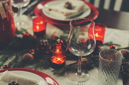 Ajuste de la tabla para la celebración de Navidad y Año Nuevo. Mesa roja y verde tradicional festiva en casa con detalles rústicos Foto de archivo