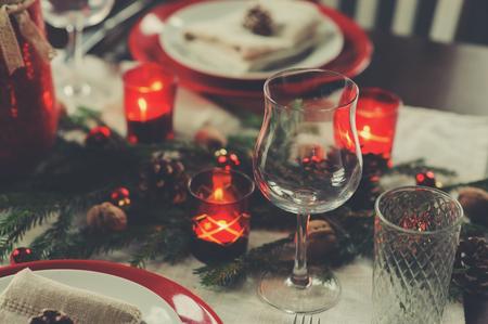Tischdekoration für Weihnachten und Neujahr. Festlicher traditioneller roter und grüner Tisch zu Hause mit rustikalen Details Standard-Bild