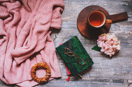 autumn or summer garden table top view with cozy sweater, coffee, glasses, sketch book, dried hydrangea flowers on wooden background