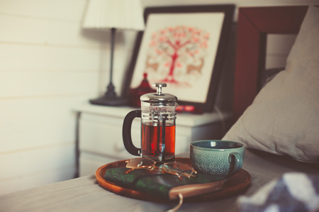 cozy winter morning at home with hot tea. Having breakfast in bed in real life interior, relaxing with book Stok Fotoğraf