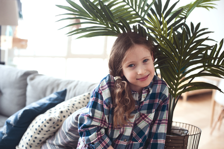happy kid girl sitting on couch near tropical house plant at home Stok Fotoğraf