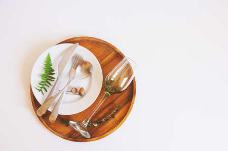 rustic table setting in natural forest style with wild ferns, wooden details and soft woodland tones. Decoration for wedding or outdoor dinner