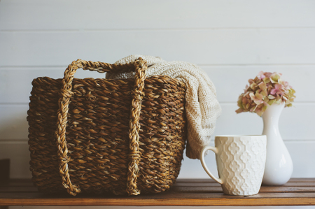 cozy winter interior details in white and brown tones. Basket with knitted sweater and cup of coffee on wooden shelf.