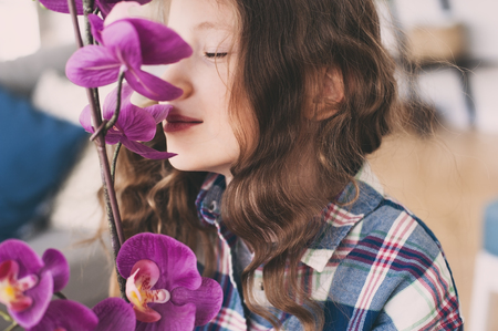 dreamy smiling kid girl smells orchid flower at home Stok Fotoğraf