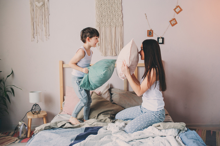 happy mother and child son playing pillow fight in bed in early morning. Family casual lifestyle series.