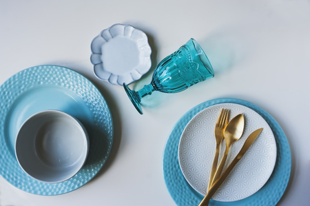 dishware winter set in blue and white tones with gold cutlery on white background. Plates, wine glass on table Stok Fotoğraf