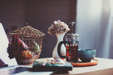 relaxing at home in cozy weekend morning. Beautiful interior details with hot tea, notes and flowers in vase Stok Fotoğraf