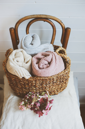 cozy still life interior details. Organizing clothes in wicker backets, seasonal wardrobe and house cleaning, ideas for winter season.