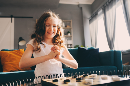 lifestyle shot of smart kid girl playing checkers at home. Board games for kids concept, candid series with real people in modern interior Stok Fotoğraf