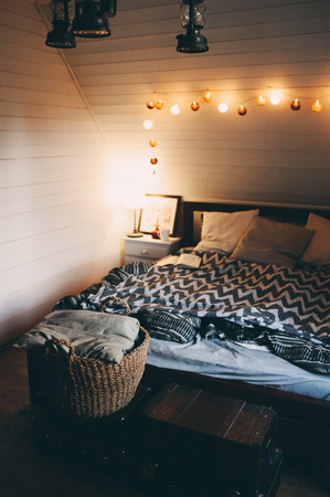 rustic bedroom with evening light in modern cottage or wooden lodge. Simple cozy living.